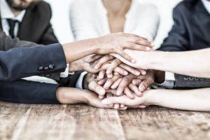 Mehrere Personen halten die Hände übereinander